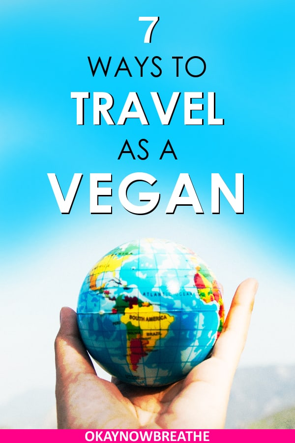 Hand holding up a tiny globe against a blue background. Title says 7 ways to travel as a vegan.
