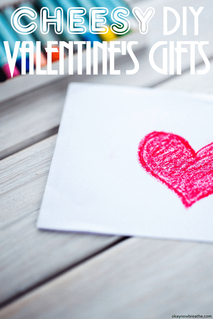 A white envelope with a crayon colored red heart in the middle. Text overlay says cheesy DIY Valentine's Gifts