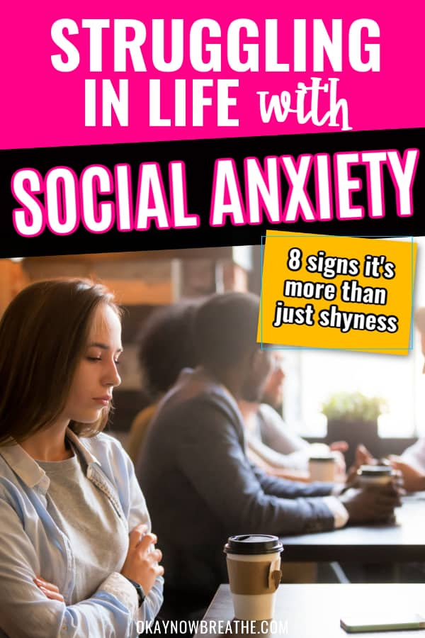 Female alone at table with a crowded table next to here. She's looking down. Text says struggling in life with social anxiety: 8 signs it's more than just shyness