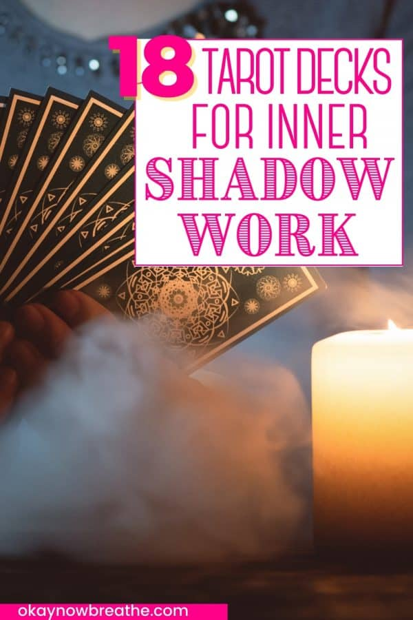 Back of tarot decks held in hand. Cards are black with gold shapes on it. There is a candle illuminating picture. There is a cloud of smoke at bottom of picture. Title text says 18 tarot decks for inner shadow work - okaynowbreathe.com