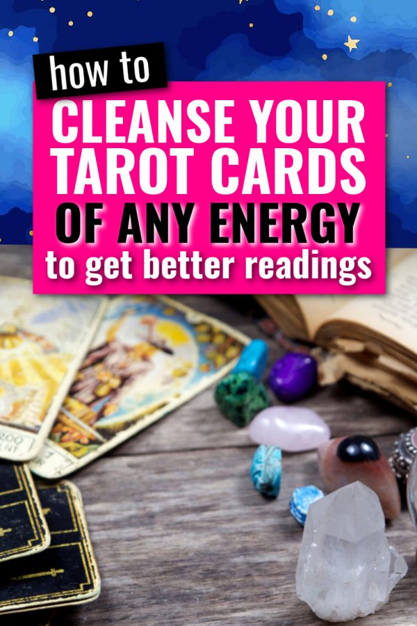 There are tarot cards and various crystals on a gray wood table. There is text in a pink box that says how to cleanse your tarot cards of any energy to get better readings